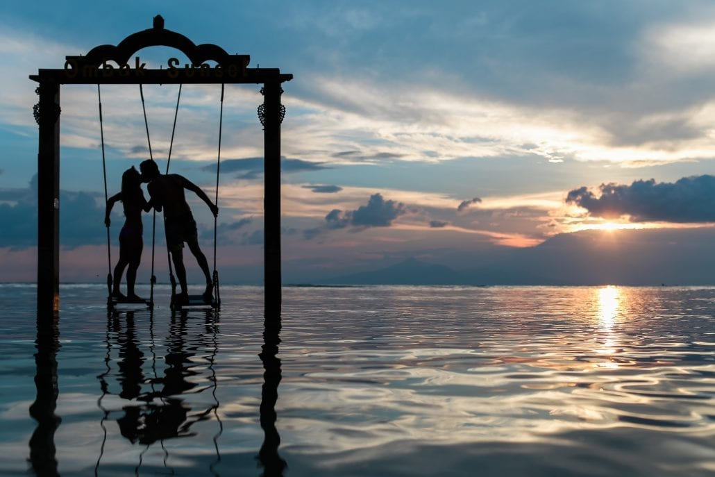 Silhouette of two lovers standing on a giant swing in the sea at sunset